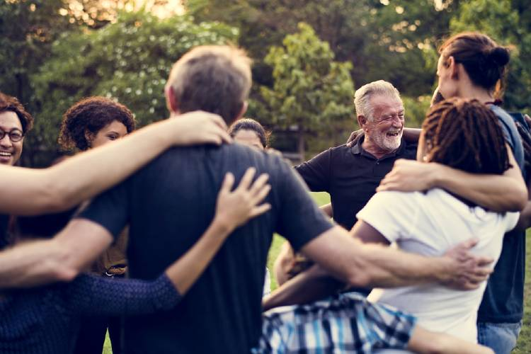 personas de todas las edades se abrazan al aire libre