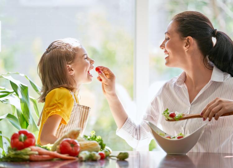 Niña come con su madre