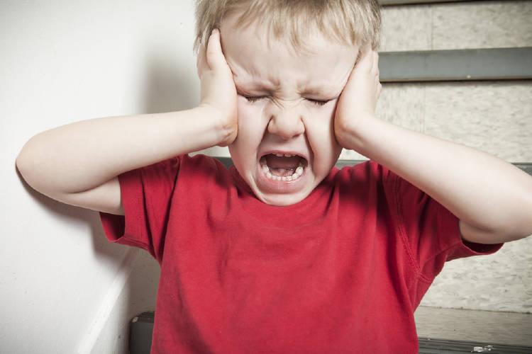 niño llora y se tapa los oidos