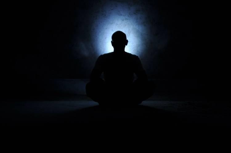 Una persona meditando en la oscuridad con una luz que irradia de su cabeza