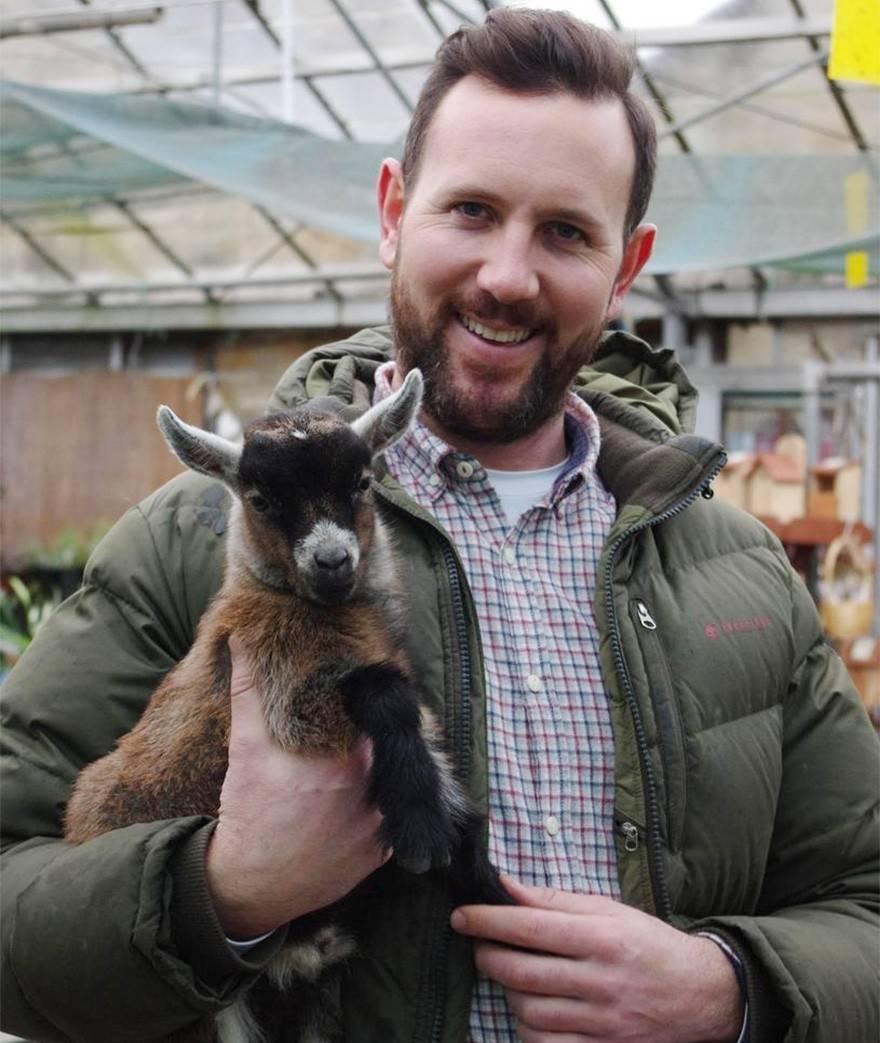 Un hombre cría a una cabra bebé rechazada por su madre