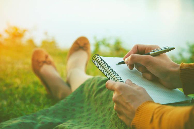 una mujer escribe en un parque