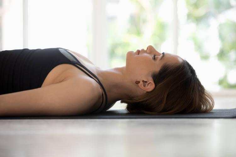 mujer practica yoga nidra tumbada sobre la esterilla de yoga