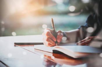 Una persona escribe su diario a la luz del sol.