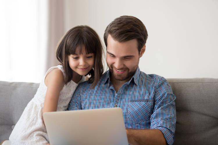 padre e hija sonrientes miran la pantalla de la computadora