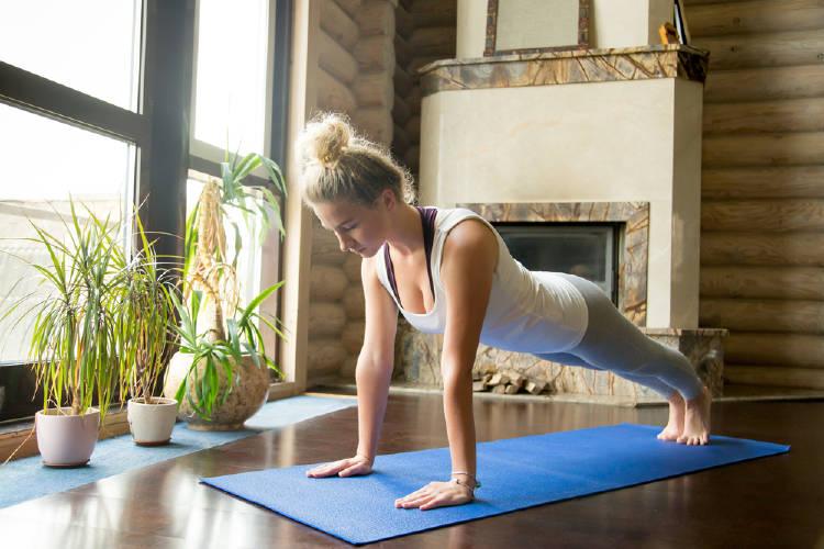 Una mujer haciendo flexiones de brazos en su casa