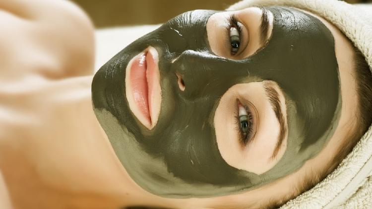 Mujer acostada con mascarilla verde en todo el rostros y toalla envolviendo su cabello