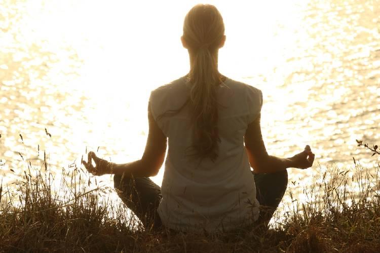 Una mujer medita frente a un lago al atardecer