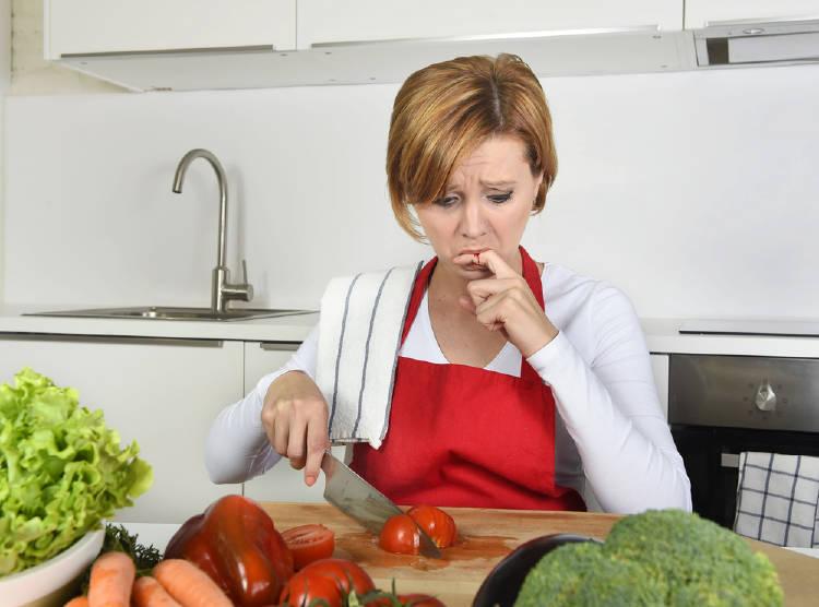 Una mujer se corta el dedo picando verdura