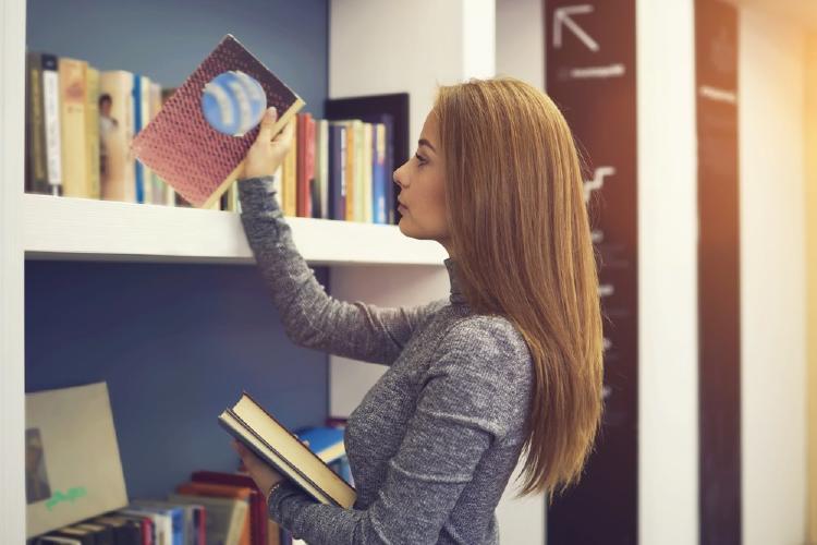 Mujer acomodando libros