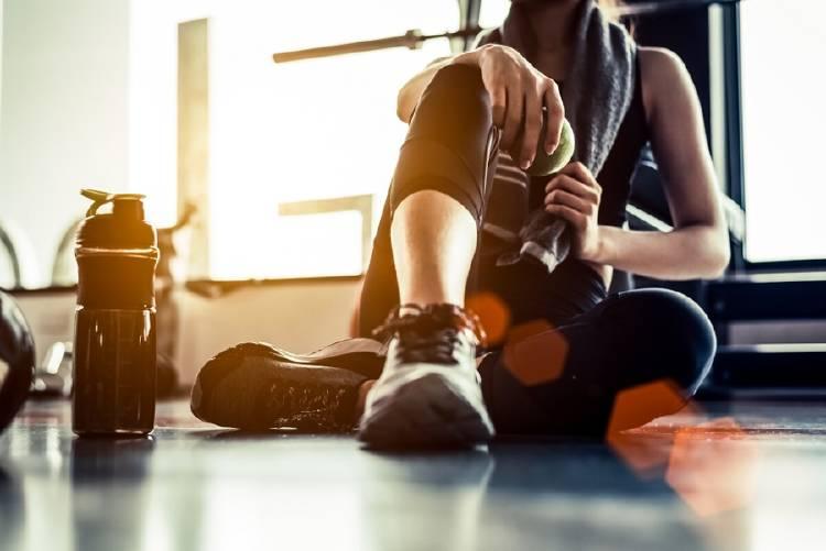mujer descansa con termo de agua luego de hacer ejercicio