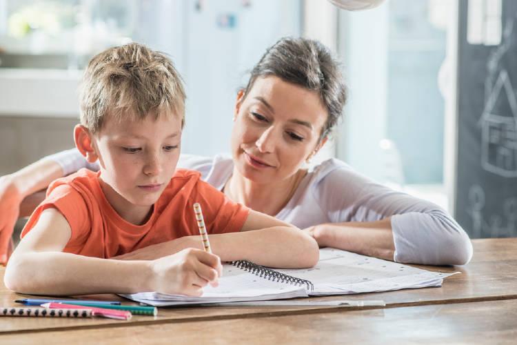 Un niño hace la tarea con su madre