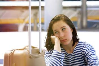 mujer con su valija espera cansada en el aeropuerto