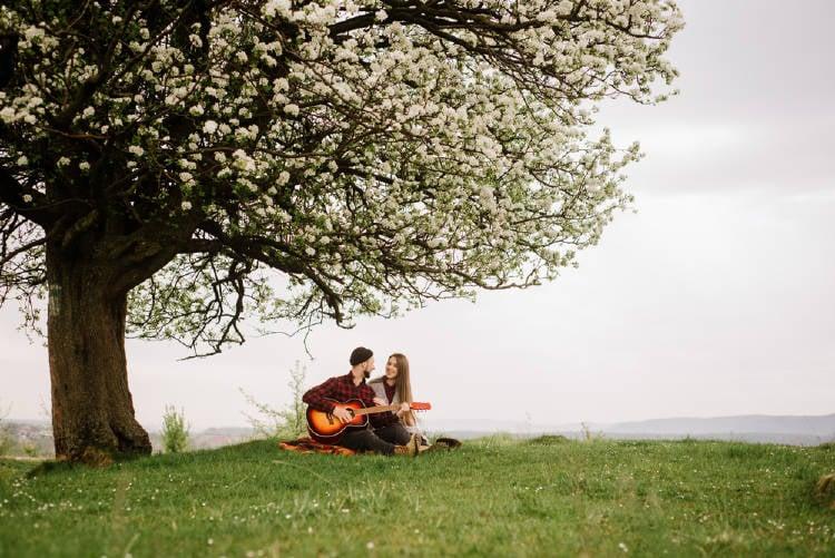 Una pareja sentada debajo de un árbol