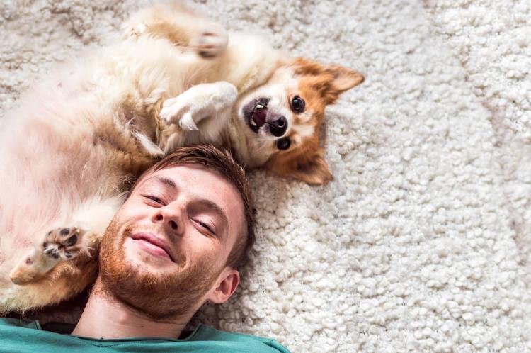 Un hombre recostado en el suelo con su perro