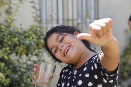niña sonríe con un vaso de agua