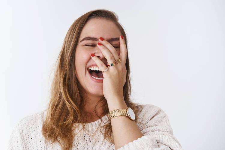 mujer de pelo rubio vestida de rosa se ríe a carcajadas