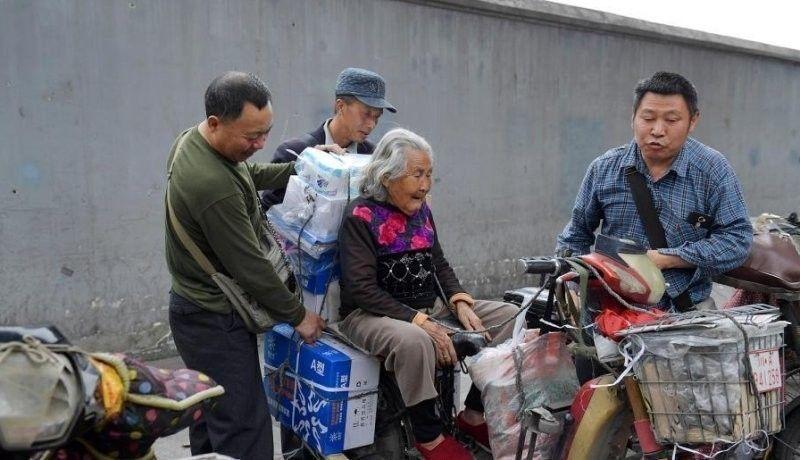 Cai Yujun lleva a su madre en moto mientras trabaja como repartidor