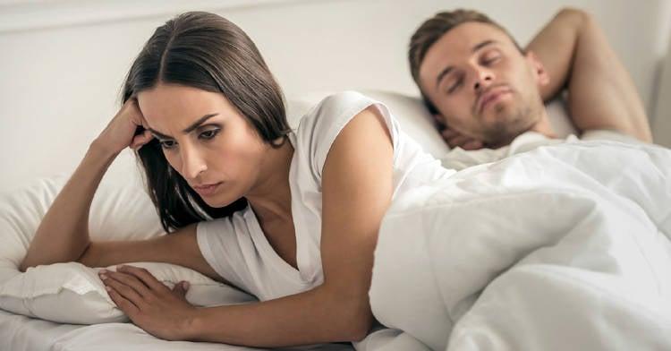 mujer enojada con su pareja en la cama