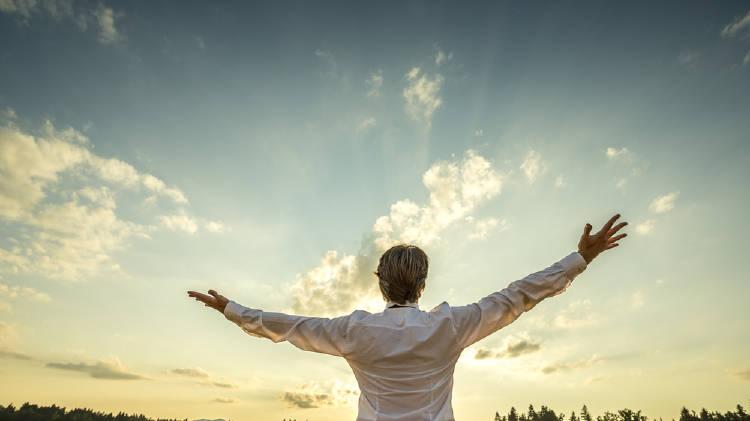 persona abriendo sus brazos mirando hacia el cielo