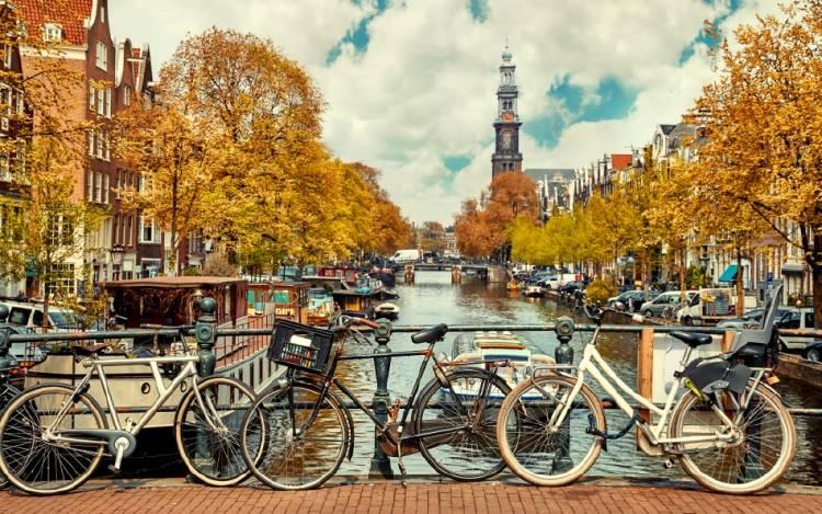 Fotografía de Amsterdam, con bicicletas apoyadas sobre el puente de un canal