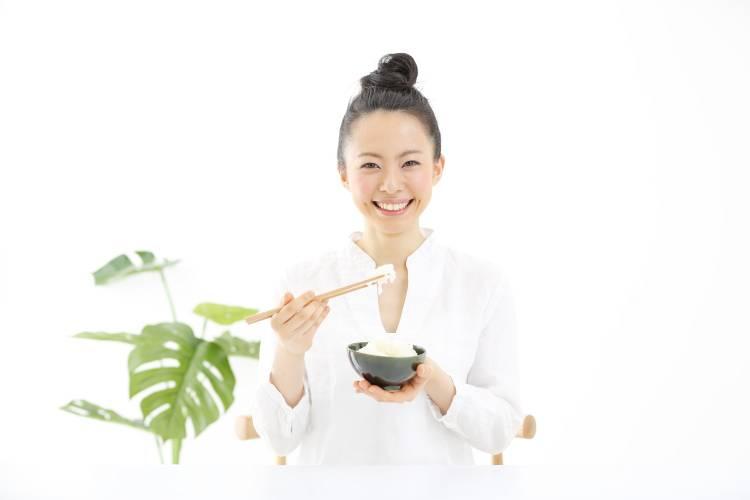mujer japonesa comiendo arroz con palitos
