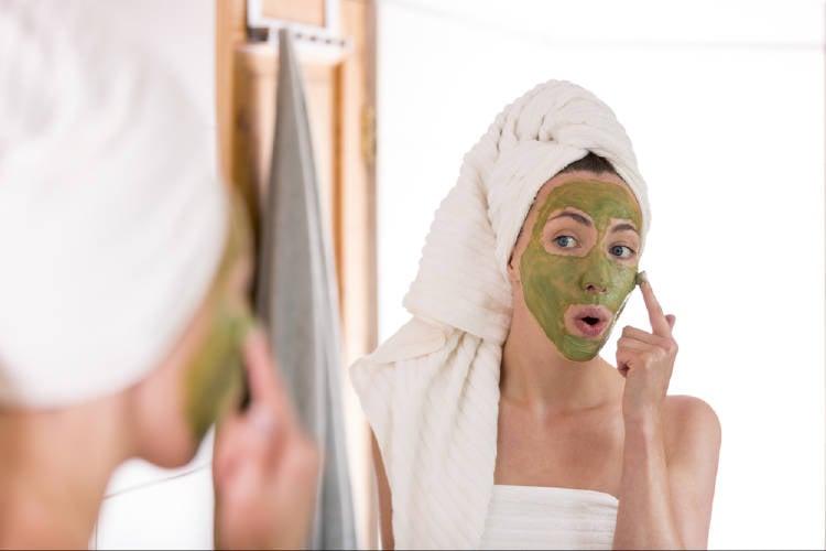 Una mujer se aplica una mascarilla verde en el rostro
