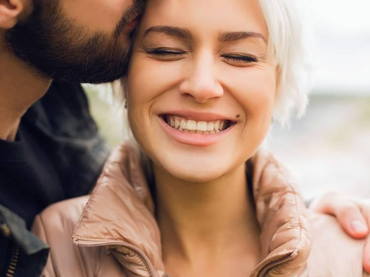 Un hombre le da un beso a su pareja y ella sonríe con felicidad