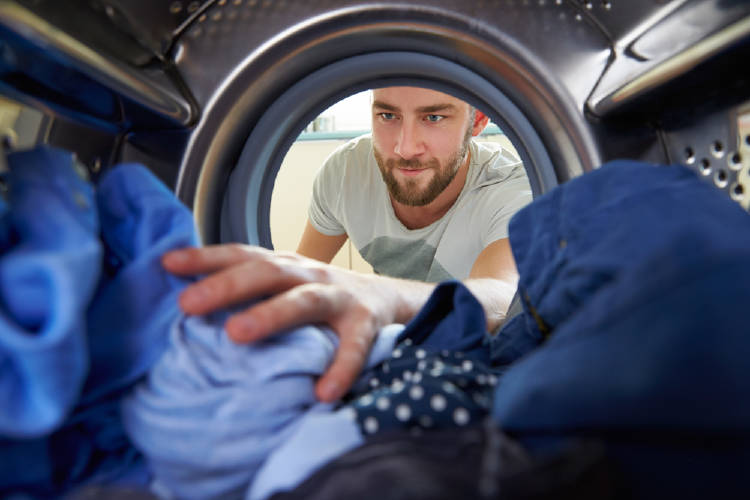 Un hombre mete ropa en la lavadora