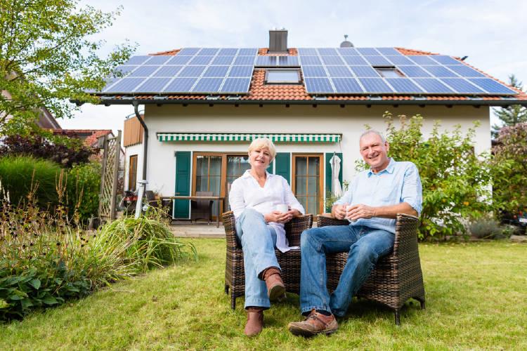 Una pareja sentada frente a una casa con paneles solares en el techo