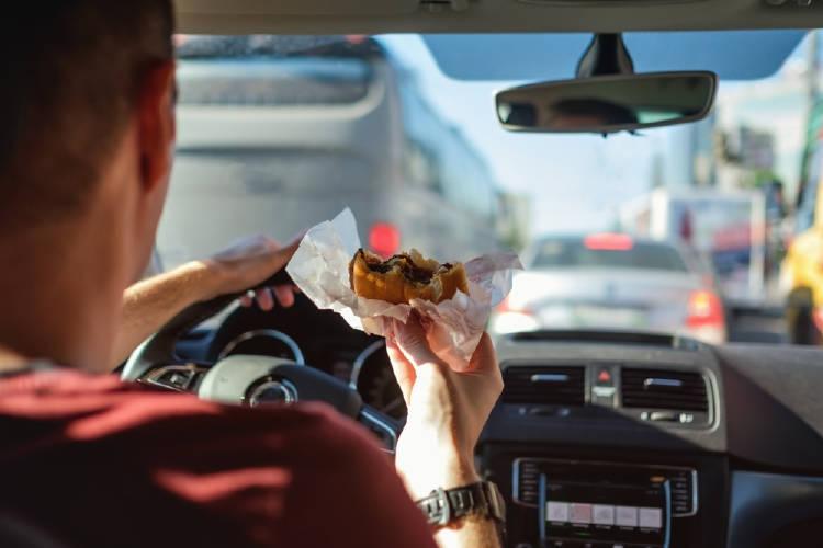 hombre come hamburguesa en el auto