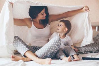madre e hijo juegan en la cama bajo las sabanas