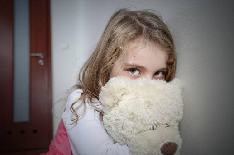 Una niña con mirada triste abraza su oso de peluche