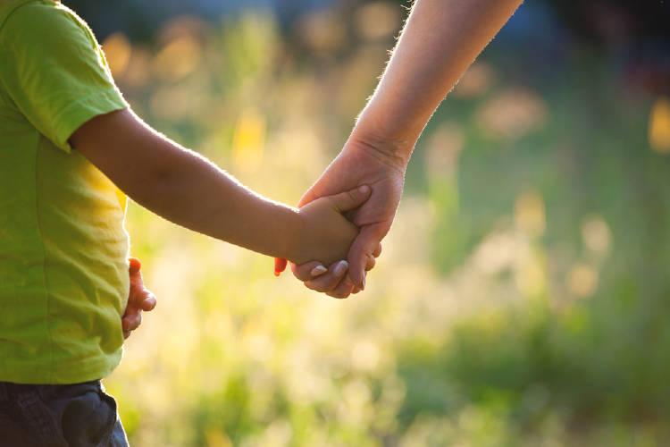 Una madre de la mano con su hijo