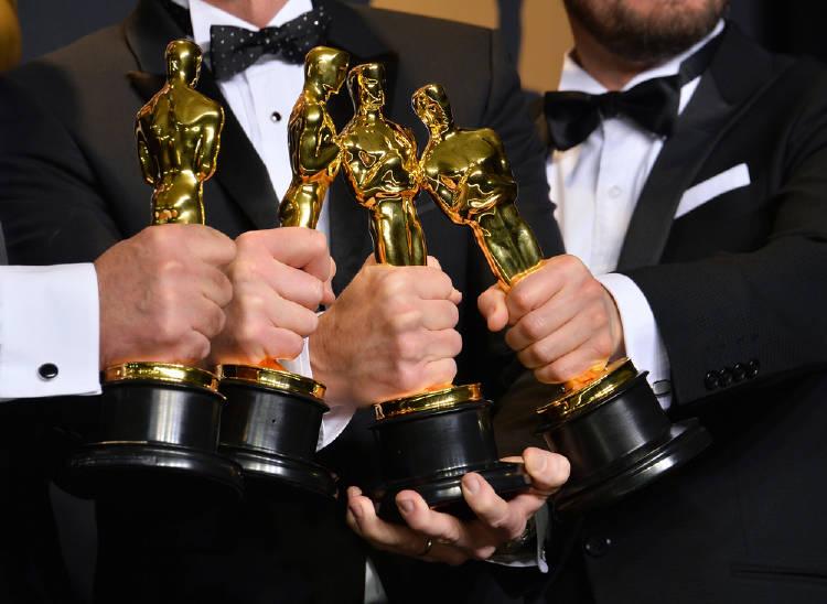 actores sostienen estatuillas en la gala de los premios oscars