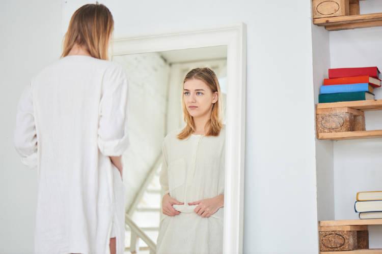 Una mujer se mira en el espejo disgustada por su apariencia