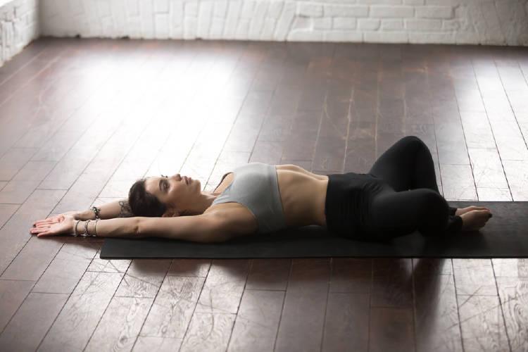 Una mujer practica la postura de yoga del zapatero tumbado