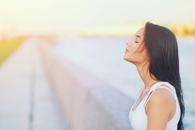 mujer respira aire fresco en la naturaleza y libera el estrés