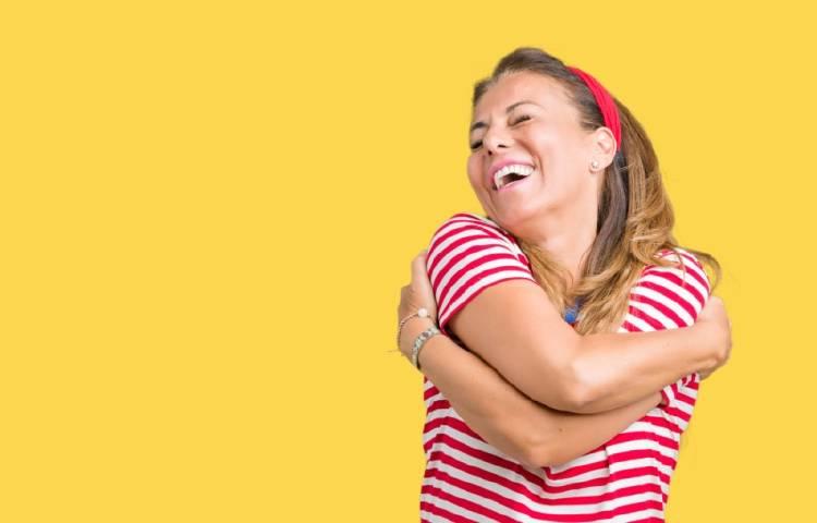 Una mujer se abraza a sí misma y sonríe