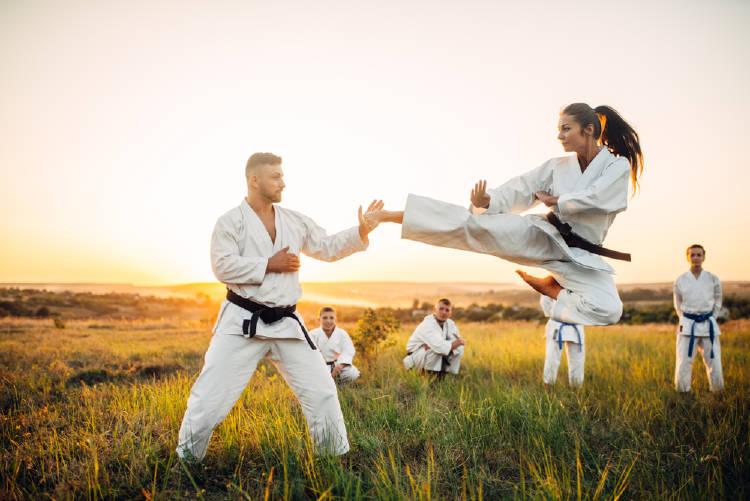 mujer y hombre practican taekwondo en la naturaleza