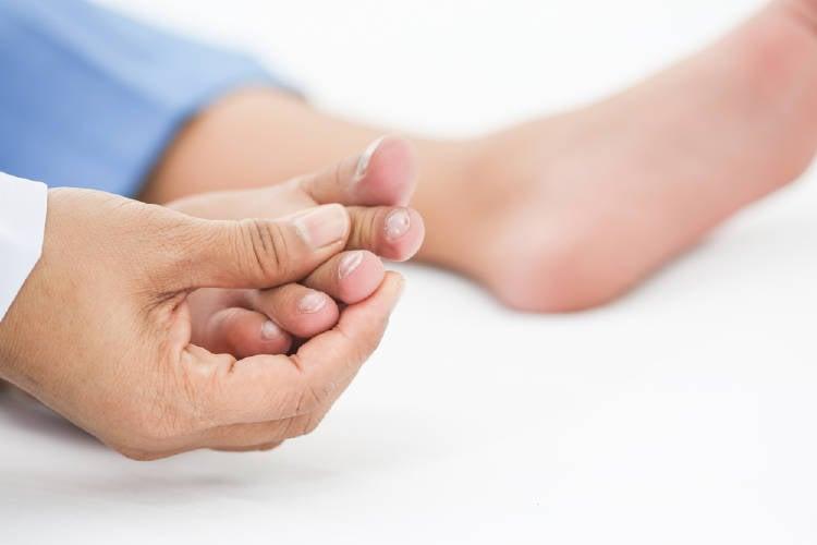 Una persona examinando las uñas de sus pies