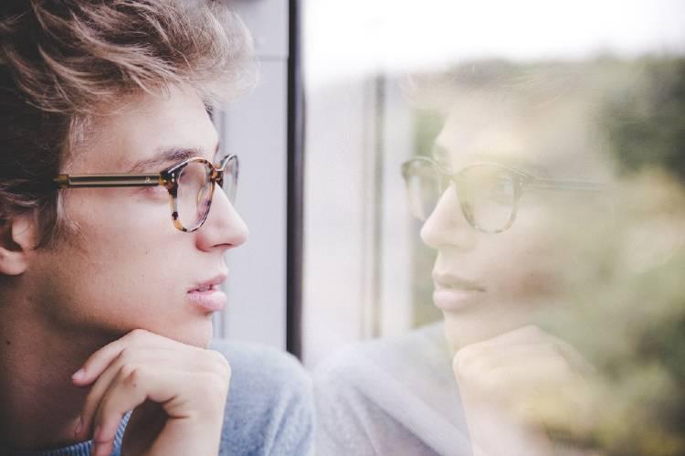 Un hombre con anteojos reflexivo mira por la ventana