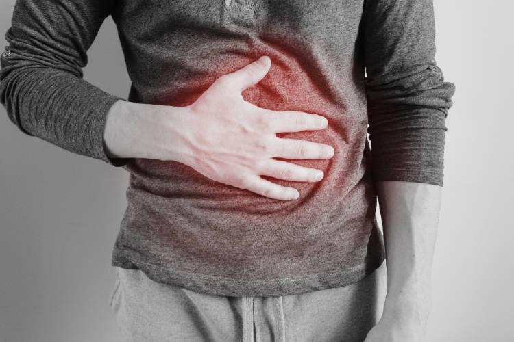 Un hombre se agarra el estómago dolorido