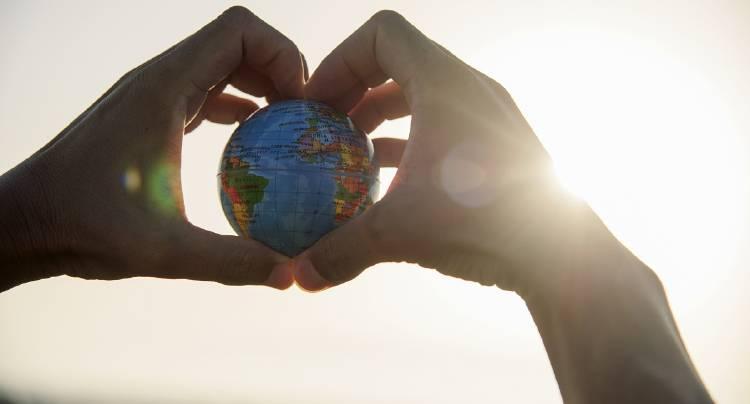 Una persona sostiene un planeta en sus manos
