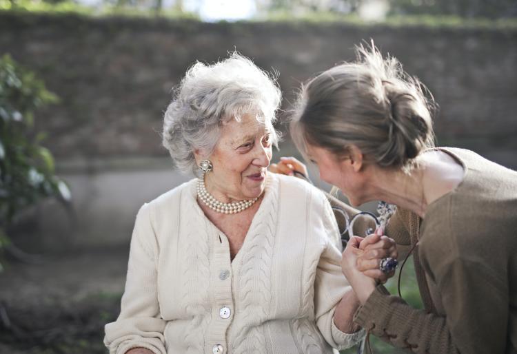 Nieta sosteniendo mano de su abuela