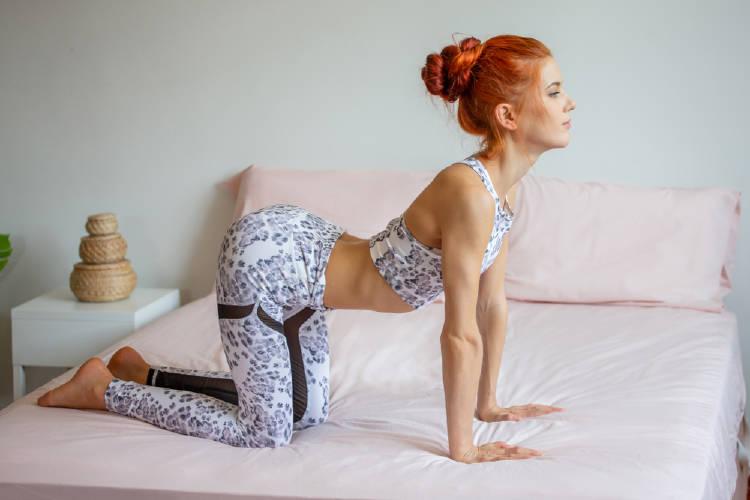 joven practica yoga en la cama estirando la columna