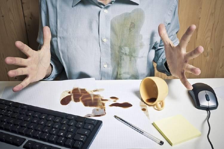 Un hombre se mancha la camisa con café