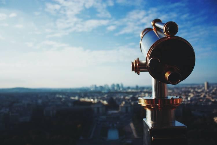 telescopio apuntando al horizonte en un día con pocas nubes y cielo azul