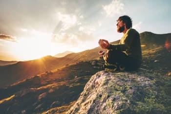 hombre medita al amanecer sobre las montañas