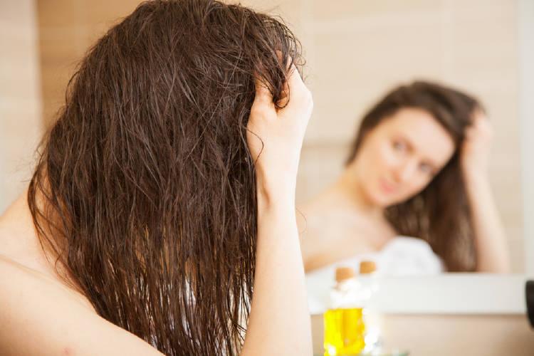 Una mujer aplica aceite en su cabello